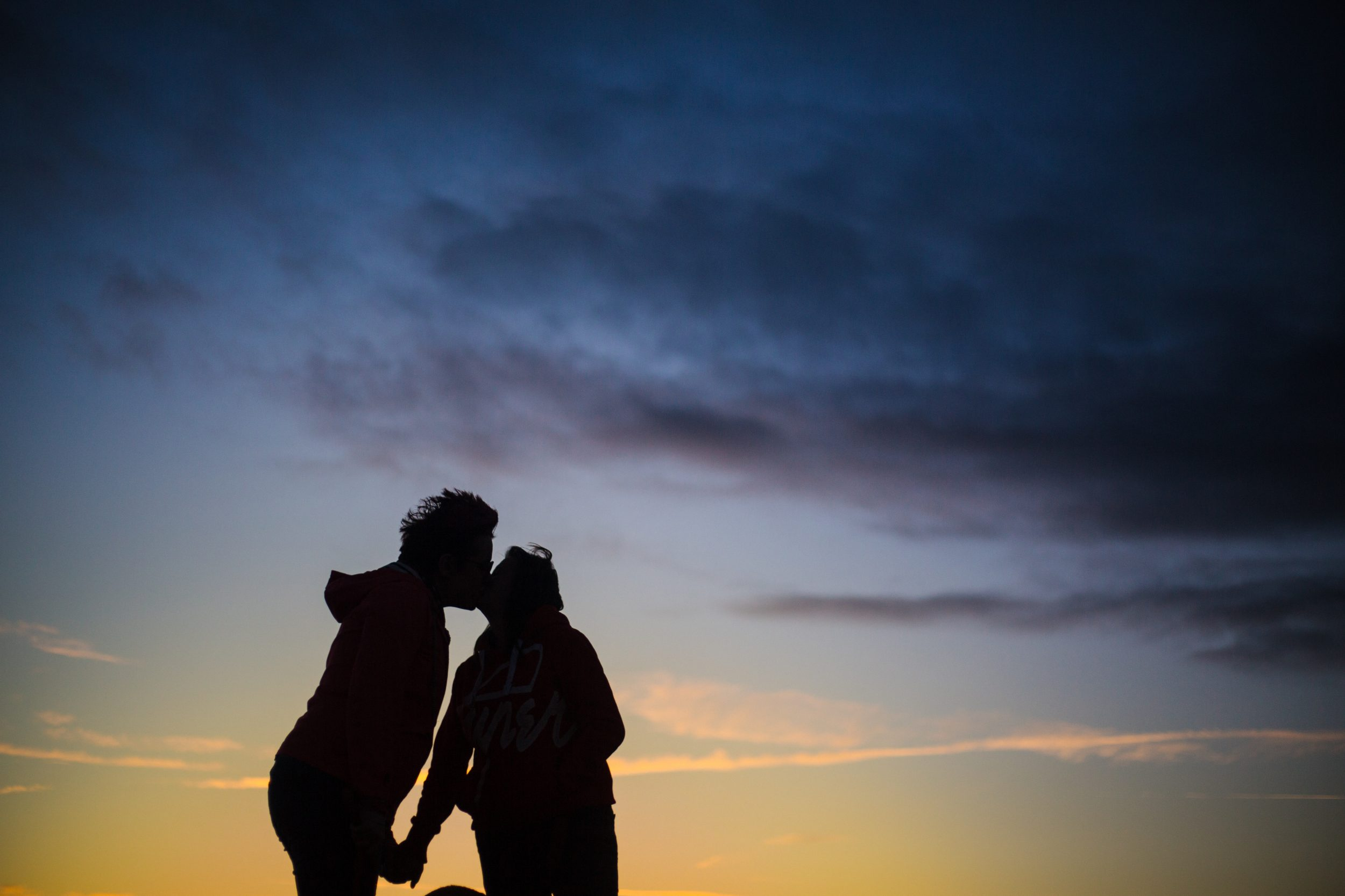 Photograph of Carrie and Amanda sharing a kiss in the sunset
