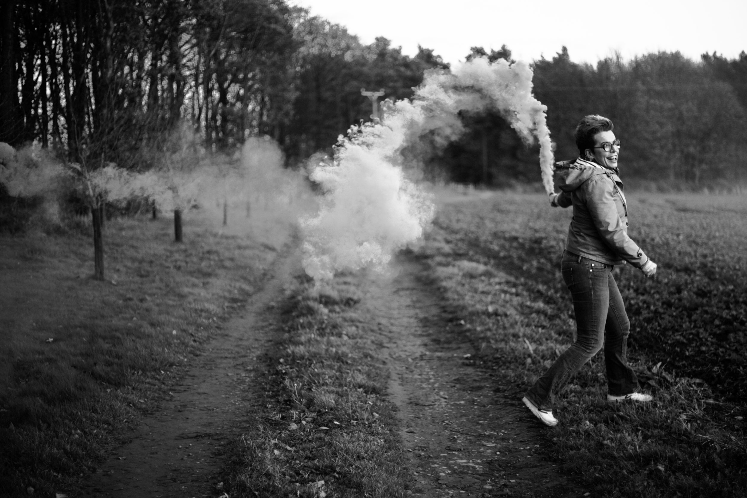 A black and white photograph of Carrie running with a smoke bomb