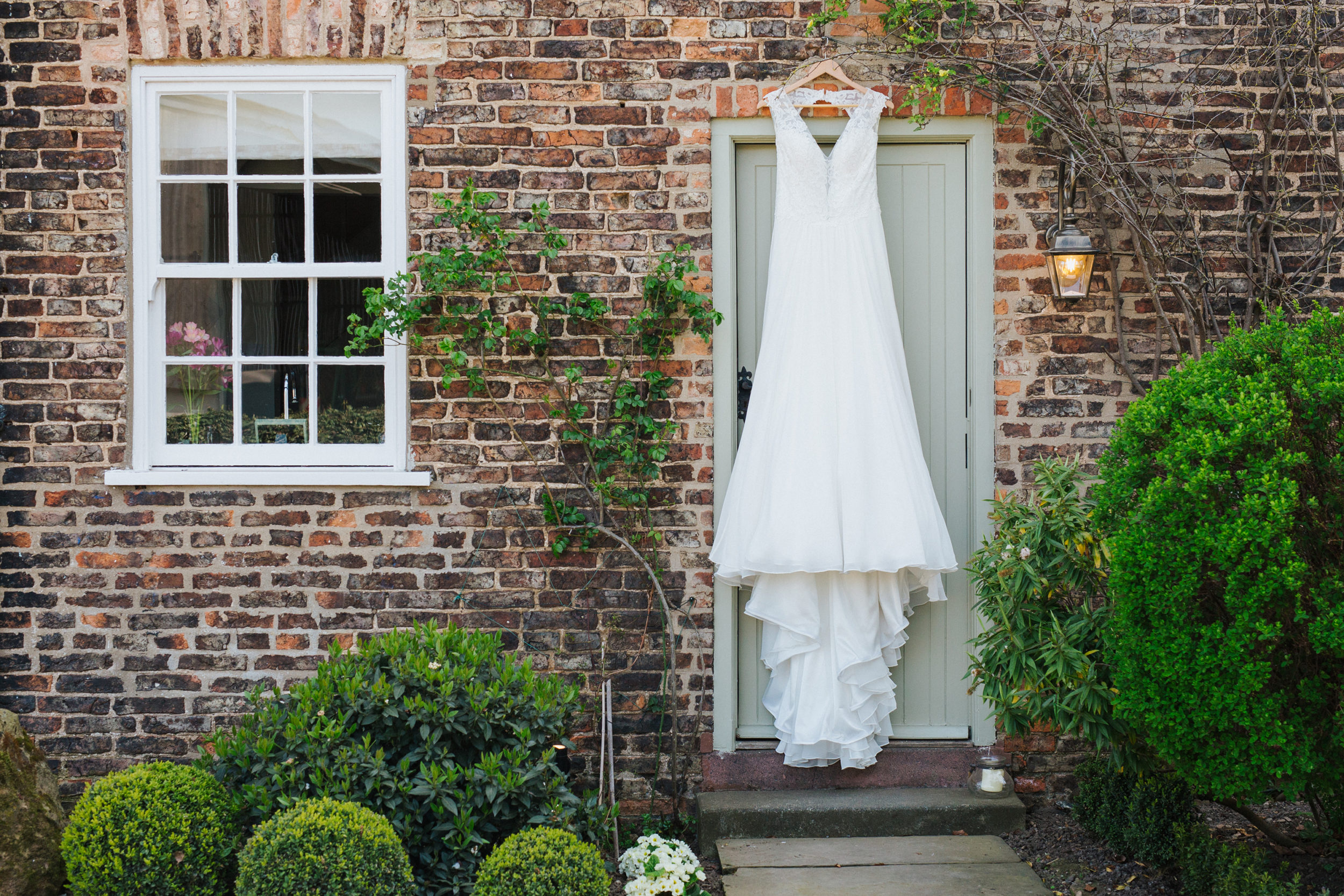 Bride's wedding dress hanging on green door outside the cottage at The Normans in York