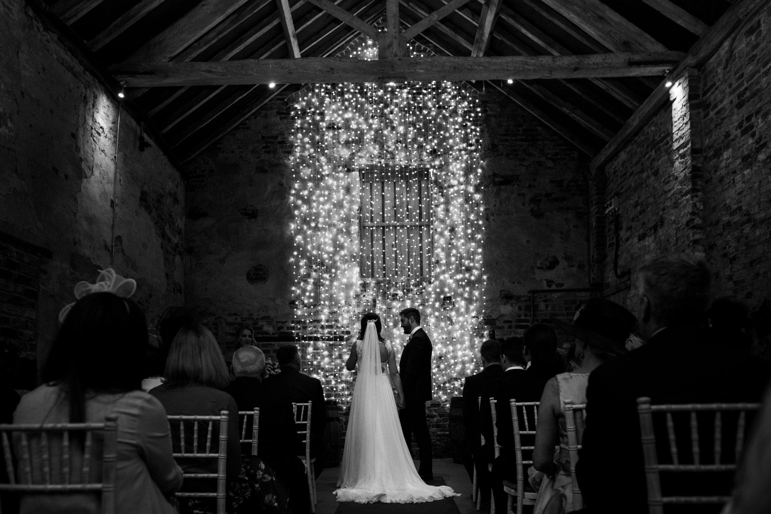 Bride and Groom exchange vows in front of fairy light wall in wedding ceremony at The Normans in York