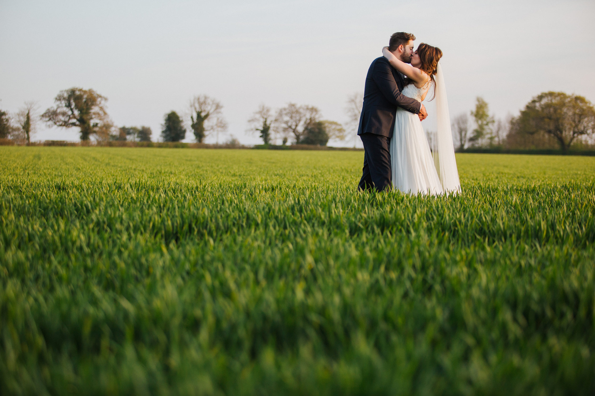 Bride and Groom share a kiss at sunset at wedding venue The Normans in York
